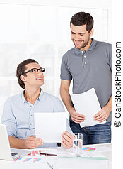 Doing some paperwork. Two cheerful business people in casual...