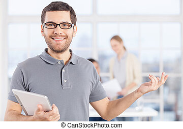 Making your business easy. Cheerful young businessman in casual wear holding digital tablet and smiling while his colleagues communicating on the background
