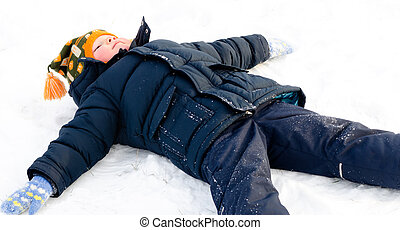 Happy little boy making snow angels in the snow lying on his...