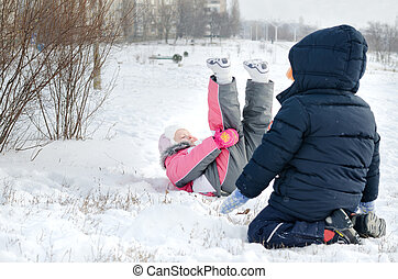 Two small children frolicking in the snow with a little girl...
