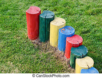 Brightly coloured tree stumps forming a barrier - Brightly...
