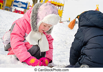 Cute little girl gathering snowballs in the snow - Adorable...