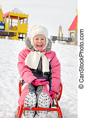 Pretty little girl playing on a sled in the snow