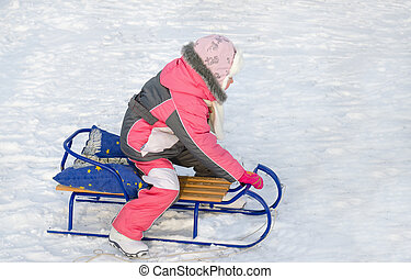 Little girl in pink playing on a toboggan