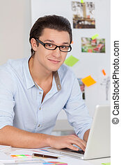 I have so many ideas. Handsome young man in glasses working on computer and smiling at camera while sitting at his working place