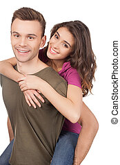 Beautiful loving couple. Cheerful young loving couple hugging and smiling at camera while standing isolated on white