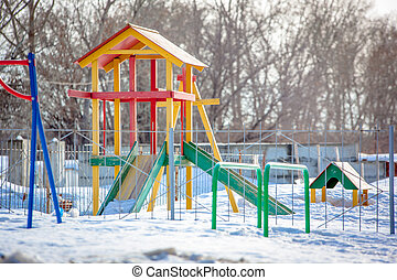 Playground with slides and swings in park in the winter