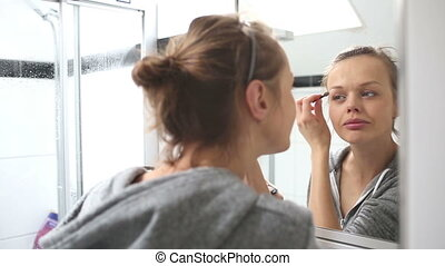 Young woman putting on make-up