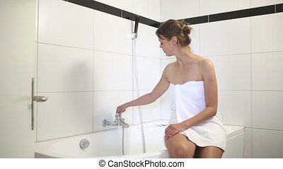Young woman sitting on a bathtub preparing a bath for...