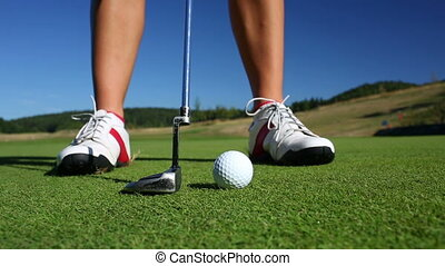 The Putting Green. Close-up view of a golf player as she...