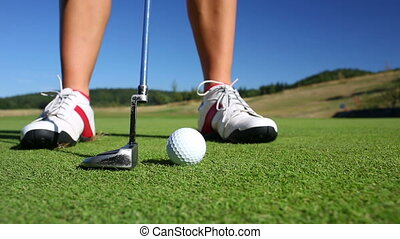 The Putting Green Close-up view of a golf player as she puts...
