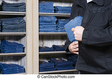 shoplifter stealing denim - jeans being stolen by a...
