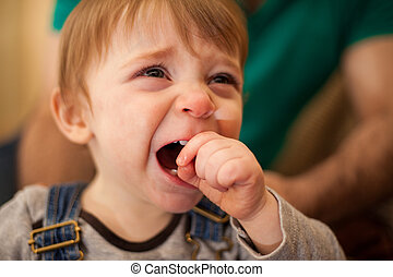 Adorable blond baby crying at home