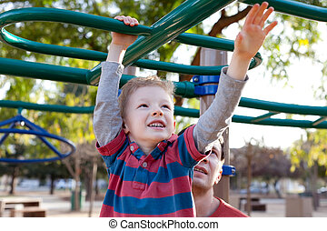 family at kids playground - little positive boy at the...