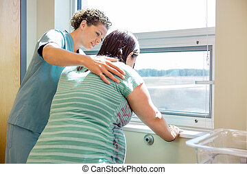 Nurse Comforting Tensed Pregnant At Window In Hospital Room...
