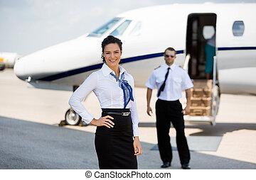 Confiado, Stewardesses, sonriente, con, piloto, y, privado,...