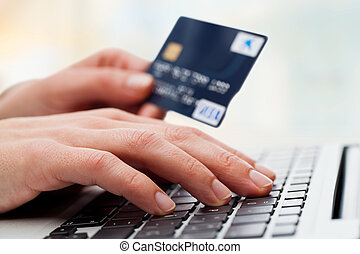 Hand typing on laptop with credit card. - Extreme close up...
