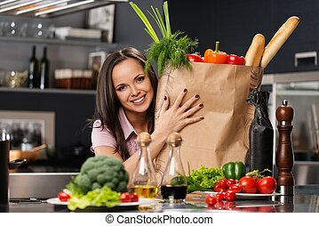 Young woman with grocery bag full of fresh vegetables on a...