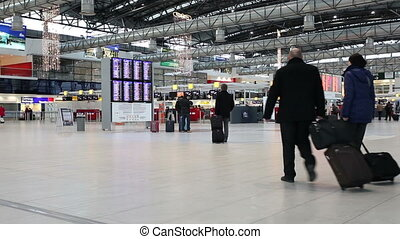 Airport rush: people with their suitcases in a modern...
