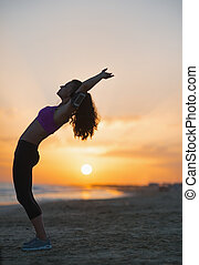 Silhouette of fitness young woman stretching on beach at...
