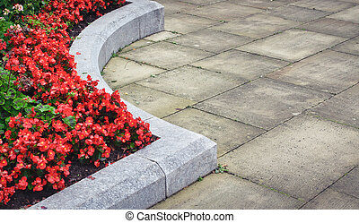 Flower bed - Red flowers in a concrete flower bed in a town