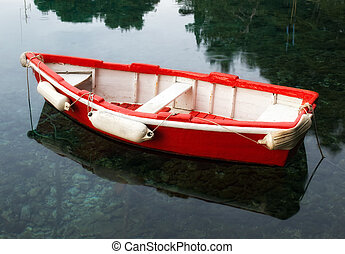 Red wooden boat - Old retro wooden boat on a calm sea...