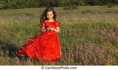 Gathering flowers - Little girl in a red dress gathering...