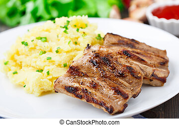Grilled ribs with mashed potato on a plate
