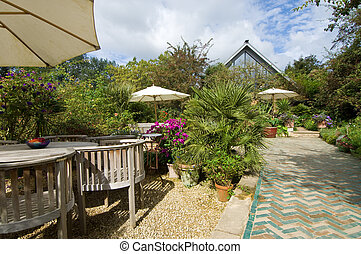 Tea Garden - The chairs and tables underneath parasols in a...
