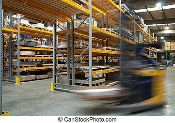 A forklift driving through a warehouse - a forklift captured...