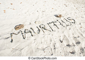 Mauritius written in pebbles on a sandy beach