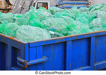Dumpster recycling - Dumpster container with green bags for...
