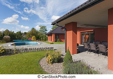 Garden pool and house - A garden of a rich house with a...