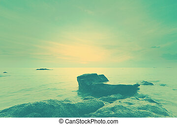 Seascape sunset with fantastic rock surface with vintage...