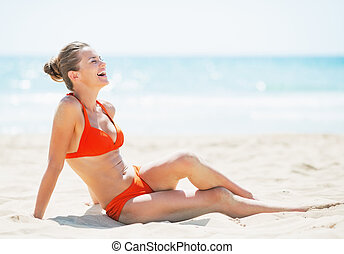 Smiling young woman laying on beach