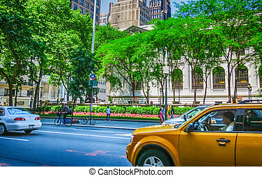 Yellow cabs speeding up in front of New York Public Library