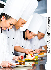 Asian Chefs in restaurant kitchen cooking - Asian Indonesian...