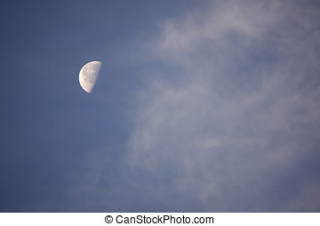 Half Moon - Half moon in blue sky with whispy clouds