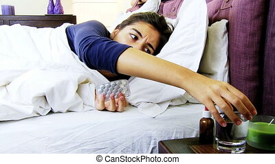 Woman with flu taking aspirin - Woman in bed feeling sic...