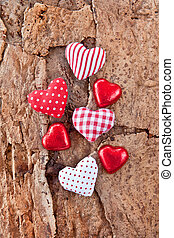 Little hearts and chocolates on wooden background