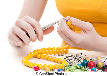 Yellow bead necklace - A woman making a wooden yellow bead...