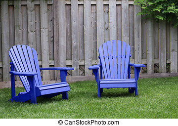 Blue Adirondack Chairs - Two blue adirondack chairs on green...