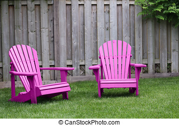 Pink Adirondack Chairs - Two pink adirondack chairs on green...