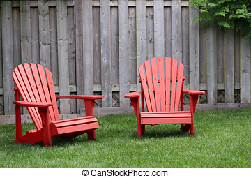 Red Adirondack Chairs - Two red adirondack chairs on green...