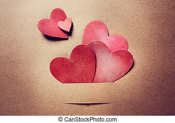 Paper cut red hearts on earthy colored paper