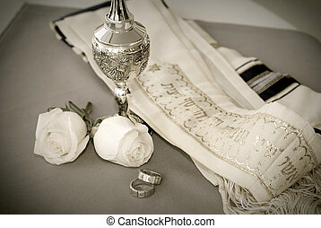 Jewish wedding rings with silver wine cup and prayer shawl.