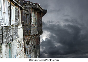 Gray moody sky - spooky old tatty wooden building on gray...