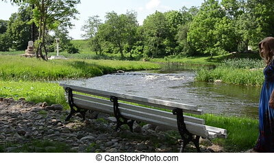 park bench river - on the edge of the white bench sits down...