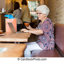 Senior Woman Using Laptop While Having Coffee In Cafeteria -...