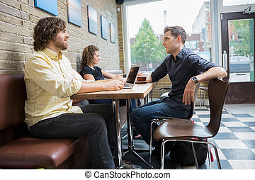 Friends Spending Leisure Time In Cafe - Male and female...